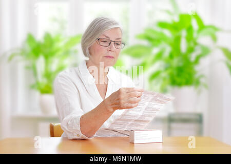Senior woman sitting at a table in her living room reading the information sheet of her prescribed medicine - Stock Photo