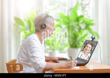 Senior woman in her living room in front of a laptop making notes during a video call with her female doctor - Stock Photo