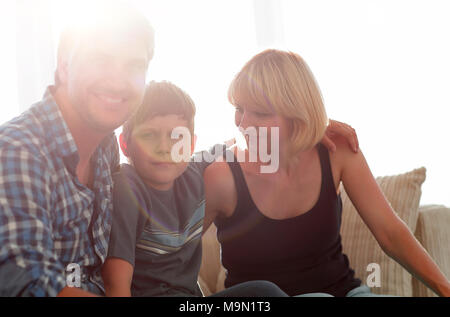 Parents and their son sit huddled in the living room and smiling - Stock Photo