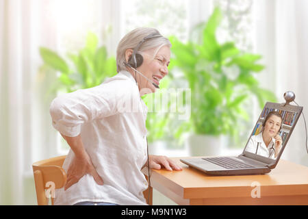Senior woman with low back pain in her living room in front of a laptop making notes during a video call with her female doctor - Stock Photo