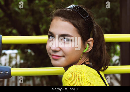 A teenage girl in a yellow sweater listens with headphones to the story of a guide sitting on the top floor of a tour bus in Paris. - Stock Photo