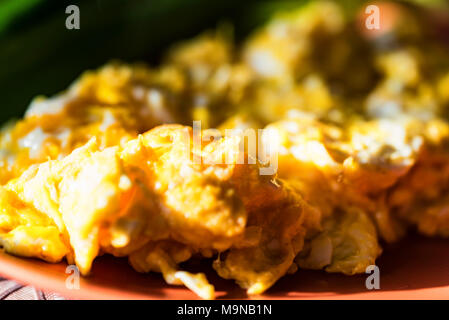 Scrambled eggs with green leek on plate close - Stock Photo