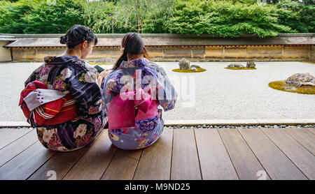 KYOTO, JAPAN - JUNE 7: Unidentified women dress in traditional clothes and observe Japanese typical zen garden in Kyoto on June 7, 2015 in Japan