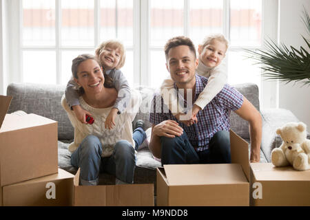 Portrait of happy young multinational family bonding together, smiling adopted kids embracing parents on couch with boxes on moving day, children hugg - Stock Photo