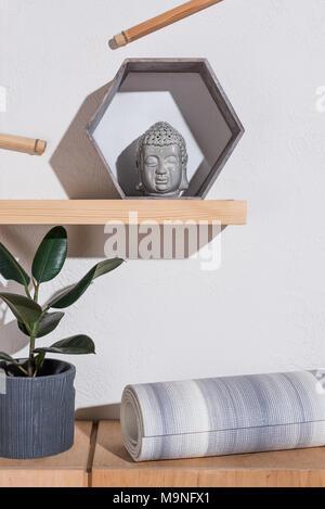 yoga mat under sculpture of buddha head in frame - Stock Photo