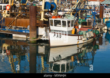 Fishing boats and their reflections while at their moorings in Camber Dock by Spice Island in Old Portsmouth, Portsmouth, on a calm day - Stock Photo