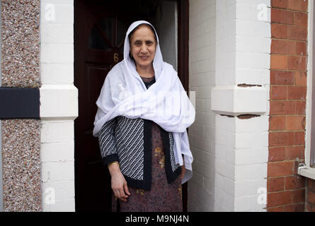 Pakistani Woman, wearing headscarf, standing in door-way of home - Rugby, England - Stock Photo