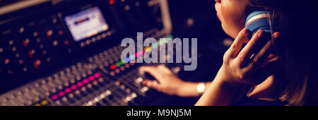 Female audio engineer listening to headphones - Stock Photo