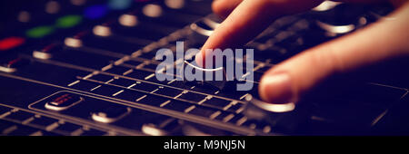 Cropped hand of audio engineer operating sound mixer - Stock Photo