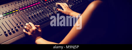 Female audio engineer using sound mixer - Stock Photo
