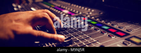 Cropped hand of musician using sound mixer - Stock Photo