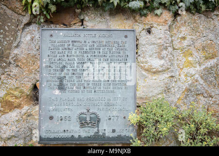 Plaque on a wall in the village of Hallaton explaining the annual pie scramble ritual and then the bottle (small kegs of beer) kicking contest against - Stock Photo