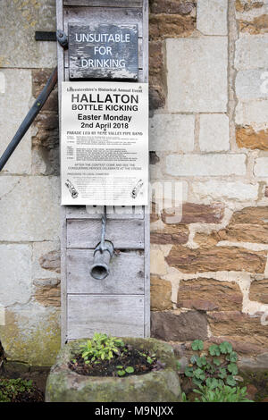 Poster on a wall in the village of Hallaton giving the timetable for the annual hare pie parade and scrambl, and then the bottle (small kegs of beer)  - Stock Photo