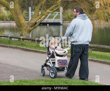 Man pushing a baby in a pushchair around a lake in a park in the UK. - Stock Photo