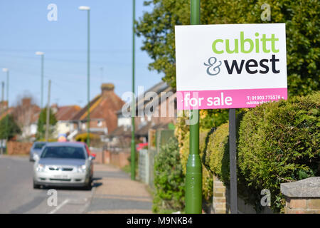 Cubitt & West estate agents 'For Sale' sign outside a house in the UK. - Stock Photo