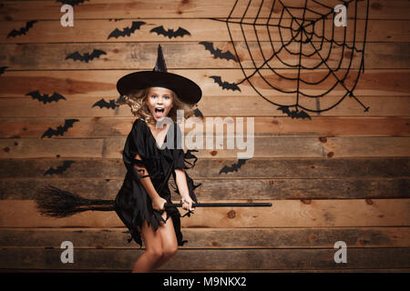 Halloween Witch concept - little caucasian witch child flying on magic broomstick over bat and spider web background. - Stock Photo