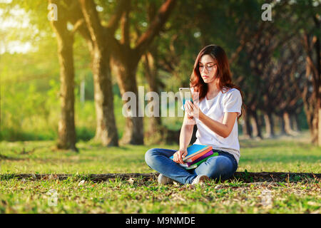 woman using moblie phone in the park - Stock Photo