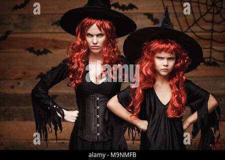 Halloween Concept - Beautiful caucasian mother and her daughter with long red hair in witch costumes with angry fussy facial expression. - Stock Photo