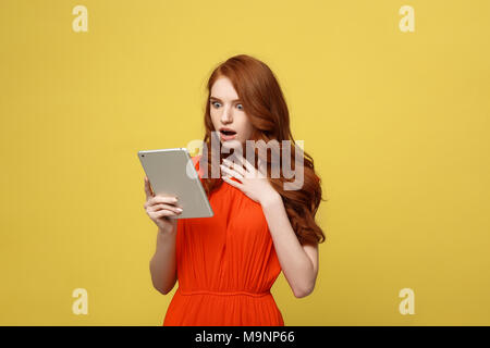 Technology and Lifestyle Concept: Surprised young woman wearing orange dress clothes using tablet pc isolated on vivid yellow background - Stock Photo