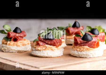 Delicious canapes with salami and spices on a wooden background - Stock Photo