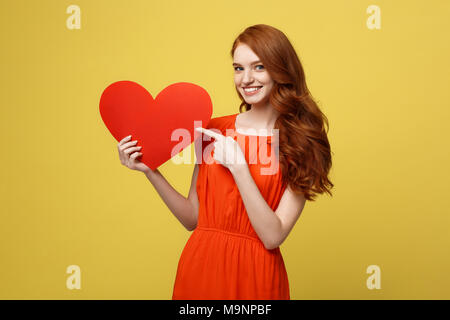 Valentine and Lifestyle Concept: Portrait of an attractive young woman dressed in red dress pointing finger at paper heart isolated over yellow studio background. - Stock Photo