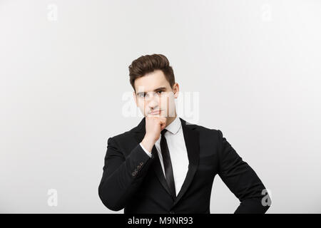 Business Concept: Portrait with copy space of handsome confident thoughtful man, holding hand on chin, standing over grey background and looking seriously to the side - Stock Photo