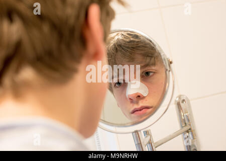 Fair-haired teenage boy looks in a bathroom mirror at his spots wearing a blackhead strip on his nose as part of a skincare routine - Stock Photo