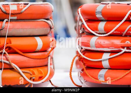 Stacked lifebuoys, livesaver, lifebelts, ring buoys - Stock Photo