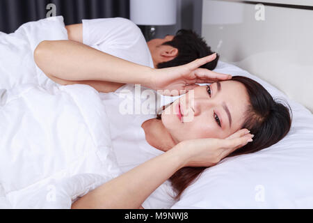 woman having sleepless on bed and having migraine,stress, insomnia, hangover in the bedroom - Stock Photo