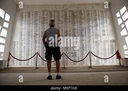 Rear view of a man standing in the shrine room, where the names of those killed on the USS Arizona are engraved on the marble wall. The USS Arizona Memorial at Pearl Harbor, Honolulu, Hawaii is final resting place for many of the ship's 1,177 crewmen who lost their lives on December 7, 1941. - Stock Photo