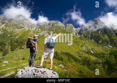 Two hikers looking at peaks of Krn mountain range in Triglav National Park, Slovenia - Stock Photo
