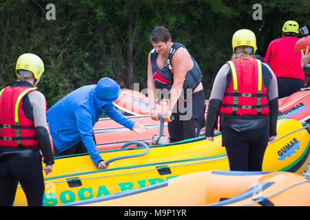 Rafting guide pumping air into inflatable boat near river Soca in Bovec, Triglav, Slovenia - Stock Photo
