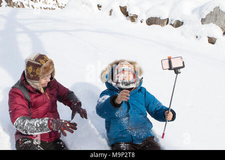 A young couple is playing in the snow in Seoraksan National Park, Gangwon-do, South Korea. The girl just threw a snowball in the face of her boy friend, who is filming with a smart phone on a selfie stick.  Seoraksan is a beautiful and iconic National Park in the mountains near Sokcho in the Gangwon-do region of South Korea. The name refers to Snowy Crags Mountains. Set against the landscape are two Buddhist temples: Sinheung-sa and Beakdam-sa. This region is hosting the winter Olympics in February 2018.   Seoraksan is a beautiful and iconic National Park in the mountains near Sokcho in the - Stock Photo