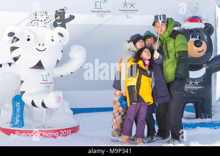 A family is taking a group selfie in Alpensia Resort, with the two mascots (Soohorang and Bandabi) of the 2018 Winter Olympics and Paralympics.  The Alpensia Resort is a ski resort and a tourist attraction. It is located on the territory of the township of Daegwallyeong-myeon, in the county of Pyeongchang, hosting the Winter Olympics in February 2018.  The ski resort is approximately 2.5 hours from Seoul or Incheon Airport by car, predominantly all motorway.   Alpensia has six slopes for skiing and snowboarding, with runs up to 1.4 km (0.87 mi) long, for beginners and advanced skiers, and an - Stock Photo