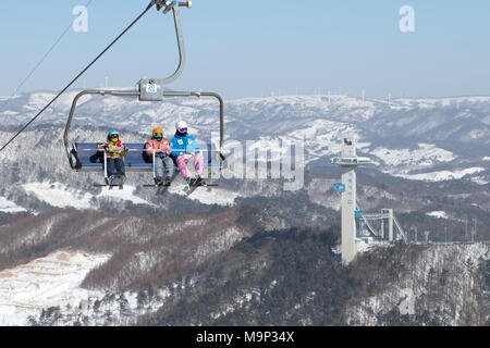 Colorful dressed skiers in a chair lift high above Alpensia resort in the Gangwon-do region of South Korea.  The Alpensia Resort is a ski resort and a tourist attraction. It is located on the territory of the township of Daegwallyeong-myeon, in the county of Pyeongchang, hosting the Winter Olympics in February 2018.  The ski resort is approximately 2.5 hours from Seoul or Incheon Airport by car, predominantly all motorway.   Alpensia has six slopes for skiing and snowboarding, with runs up to 1.4 km (0.87 mi) long, for beginners and advanced skiers, and an area reserved for snowboarders. - Stock Photo