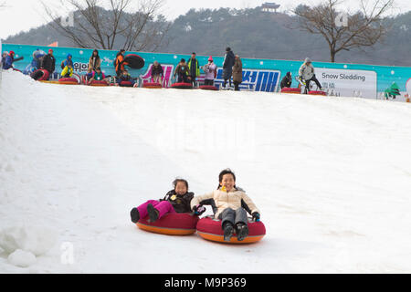 An Asian woman and her daughter are having fun sledding down a steep ice slope.   The Hwacheon Sancheoneo Ice Festival is a tradition for Korean people. Every year in January crowds gather at the frozen river to celebrate the cold and snow of winter. Main attraction is ice fishing. Young and old wait patiently over a small hole in the ice for a trout to bite. In tents they can let the fish grilled after which they are eaten. Among other activities are sledding and ice skating.  The nearby Pyeongchang region will host the Winter Olympics in February 2018. - Stock Photo