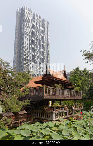 Traditional Thai wooden house on stilts in modern district, M. R. Kukrit's House, Museum, Sathorn, Bangkok, Thailand - Stock Photo