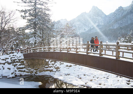 A man and woman are walking over a wooden bridge in Seoraksan National Park, Gangwon-do, South Korea.  Seoraksan is a beautiful and iconic National Park in the mountains near Sokcho in the Gangwon-do region of South Korea. The name refers to Snowy Crags Mountains. Set against the landscape are two Buddhist temples: Sinheung-sa and Beakdam-sa. This region is hosting the winter Olympics in February 2018. - Stock Photo