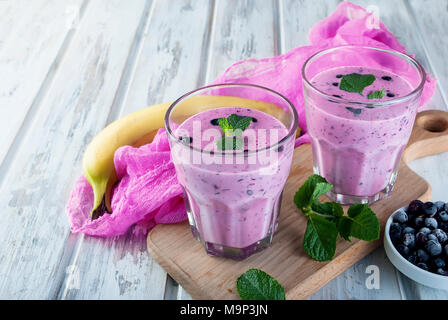 Refreshing Summer purple  smoothie or milkshake with mint, yogurt and blueberries. in glass, on wooden table, copy space, top view - Stock Photo