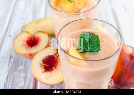 refreshing Summer smoothie or milkshake with apricot, peach and banana, mint, yogurt in glass with ingredients, on white wooden table, copy space, - Stock Photo