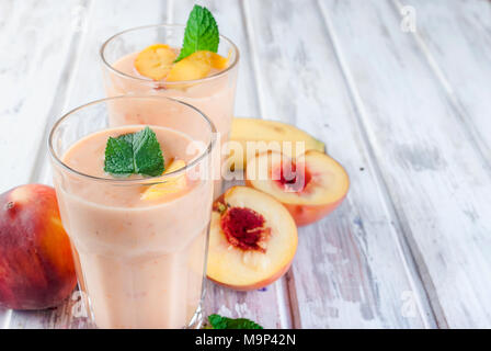 refreshing Summer smoothie or milkshake with apricot, peach and banana, mint, yogurt in glass with ingredients, on white wooden table, copy space, top - Stock Photo