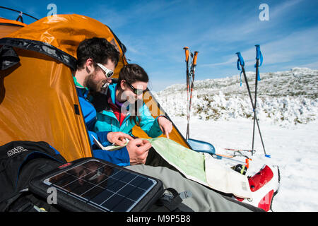 Man and woman setting up campsite in winter in mountains during daytime, New Hampshire, USA