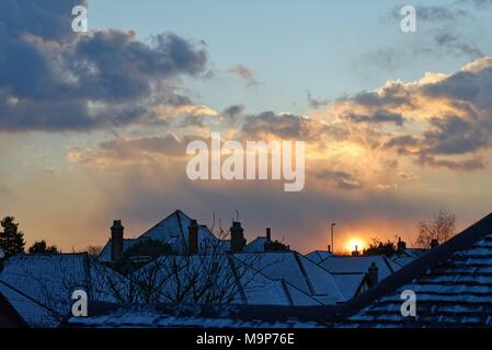 Dramatic sunset through gathering snow clouds over suburban rooftops - Stock Photo