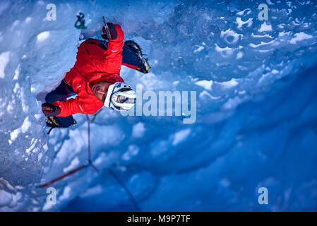 Ice climber climbing Fluido azzurro icefall, simplon pass, Valais Canton, Switzerland - Stock Photo