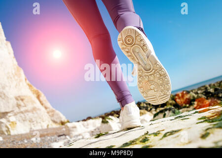 close pof the sole of a running shoe, cross country running by white cliffs along the shore and rocks. - Stock Photo