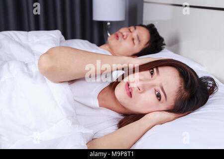 annoyed wife blocking her ears from noise of husband snoring in the bedroom - Stock Photo