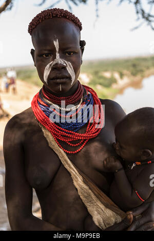 Young woman breastfeeding baby, Karo tribe, Omo River, Southern Nations Nationalities and Peoples' Region, Ethiopia - Stock Photo