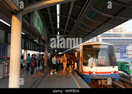 People board the BTS Skytrain in the morning, Saphan Taksin Station, Sathon, Bangkok, Thailand - Stock Photo