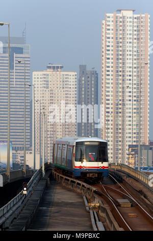 BTS Skytrain in front of skyscrapers, on Saphan Taksin Bridge, Sathon, Bangkok, Thailand - Stock Photo