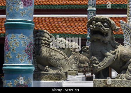 detail of statuary at the Grand Palace in Bangkok showing guardian lions, decorated blue ceramic pillar with red roof tiles in background - Stock Photo